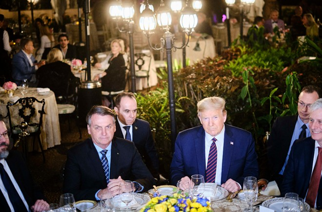 President Donald Trump and Brazilian President Jair Bolsonaro, left, during a dinner at Trump's Mar-a-Lago resort in Palm Beach, Fla., March 7, 2020. Trump's weekend getaway at the resort put him in contact with several people who later tested positive for the virus. - T.J. KIRKPATRICK/THE NEW YORK TIMES