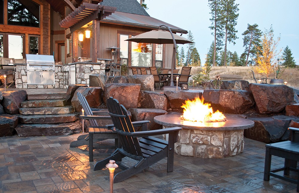 Fire draws people to relax and linger. Legacy Landscapes included a casual yet cozy firepit and a more elaborate outdoor fireplace and covered seating area in these two recent projects. - LEGACY LANDSCAPES