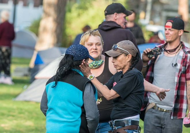 Jewels Helping Hands co-founder Julie Garcia (right) addresses a woman as formerly homeless activist Elizabeth Osborn looks on. - DANIEL WALTERS PHOTO