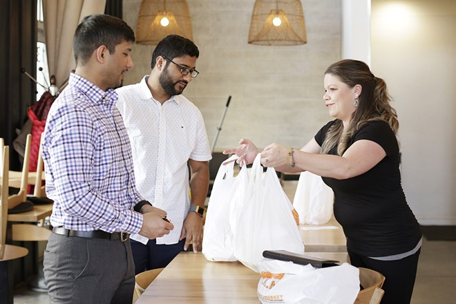 Customers pick up a takeout order at Umi Sushi Kitchen & Bar in Kendall Yards. - YOUNG KWAK