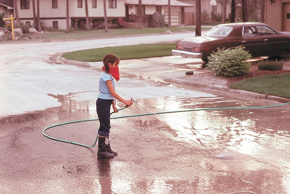 Roger Crum's young daughter Wendy washes ash away with a hose. - ROGER CRUM PHOTO