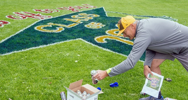 "Rogers High School art teacher Tom Pettoello grabs yet another can of spray paint to finish up a ""Hats Off To You, Class of 2020"" logo in the Clock Tower meadow in Riverfront Park. - DANIEL WALTERS PHOTO"