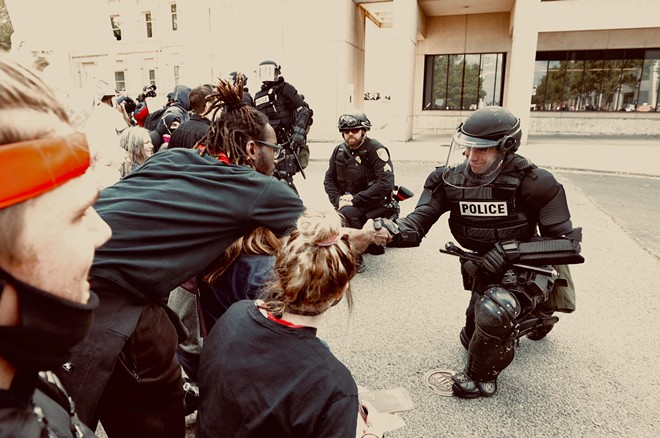Some local officers kneeled in solidarity with protesters outside the county courthouse. - YOUNG KWAK PHOTO