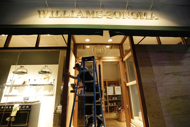 A worker boards up windows at the downtown Williams-Sonoma, hoping to deter vandals. - YOUNG KWAK PHOTO