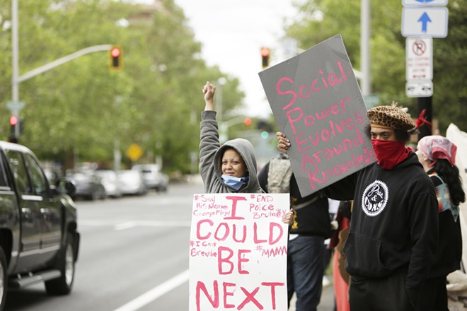 Shakayla Delcambre, left, and Lamont Higgins hold signs and gesture in front of Riverfront Park. - YOUNG KWAK PHOTO