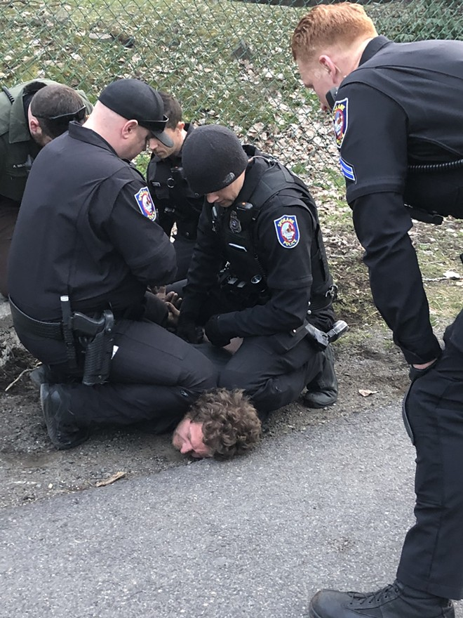 A photo, taken by witness Eddie Westerman, shows a police officer's knee on a suspect's neck. - EDDIE WESTERMAN PHOTO