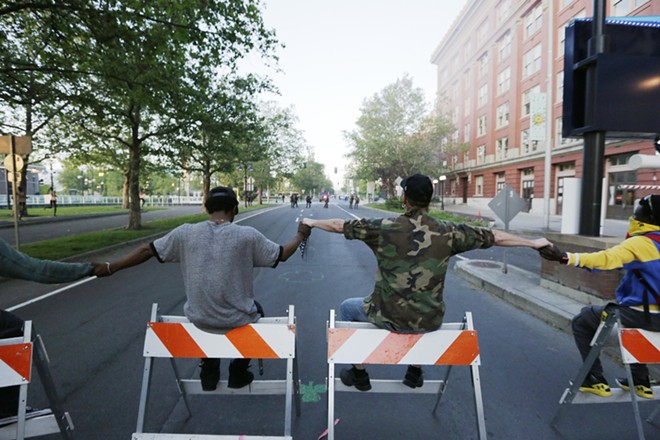 Demonstrators sit on barricades they set up on W. Spokane Falls Blvd., in front of Riverfront Park. - YOUNG KWAK