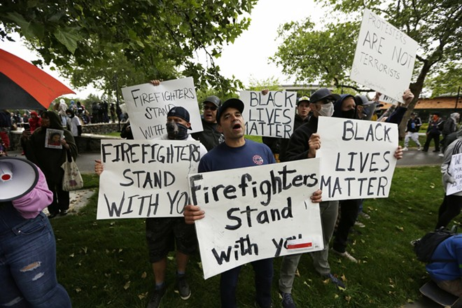 (Left to right) Spokane Fire Department Firefighter Randy Marler, Lt. Scott Coldiron, Firefighter Micah Edwards and other firefighters holds signs on W. Spokane Falls Blvd. - YOUNG KWAK