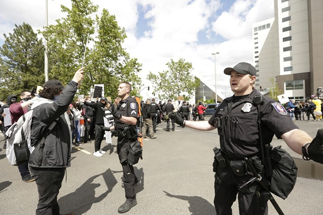 Demonstrators face-off with police at the Liberty Building parking lot. - YOUNG KWAK
