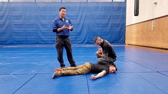 "A Washington State Criminal Justice Training Commission trainer shows a ""ground control knee placement drill"" where an officer would place their knee on the suspect's shoulder and another on the ground to gain control."