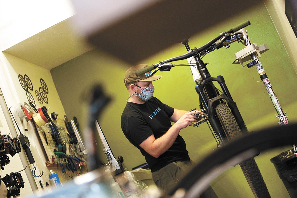 Tim Dunn, the Bike Hub's downtown store manager, works on a customer's bike. - YOUNG KWAK PHOTO