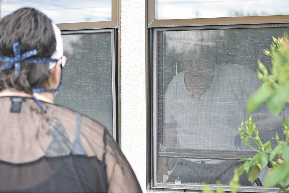 Lacy visits her dad, Butch, through the window at the Spokane Veterans Home in June. - WILSON CRISCIONE PHOTO