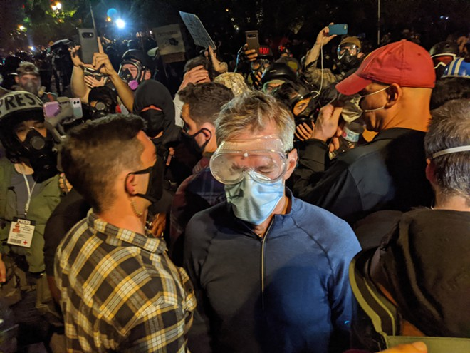 Portland Mayor Ted Wheeler wears goggles and a face mask during a protest against racial inequality and police violence in Portland, Ore. late Wednesday, July 22, 2020. Wheeler, was left coughing and wincing in the middle of his own city Wednesday night after federal officers deployed tear gas into a crowd of protesters that he had joined outside the federal courthouse. - MIKE BAKER/THE NEW YORK TIMES