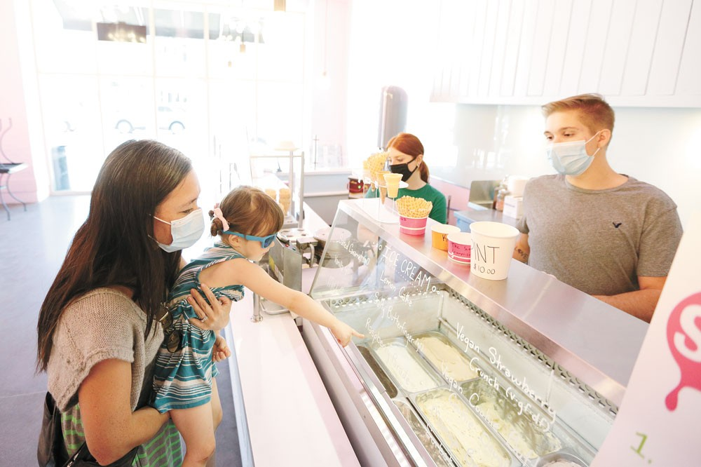Vanessa Thomsen (left) holds her 3-year-old daughter Mariko as she orders ice cream from Marlin Jones at the Scoop in Kendall Yards. - YOUNG KWAK PHOTO
