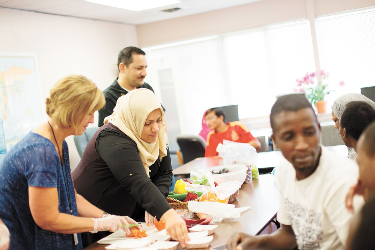 Iraqi refugee Maha Almajidi, center, helps serve tomatoes during a nutrition workshop at World Relief Spokane. - YOUNG KWAK PHOTO