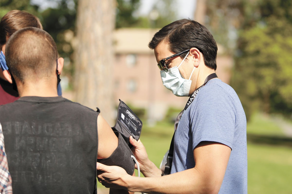 Luis Manriquez, a member of a street medicine team, prepares  to check a homeless man's blood pressure. - YOUNG KWAK PHOTO