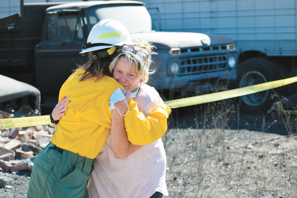 Malden Mayor Chris Ferrell (right) hugs Washington Commissioner of Public Lands Hilary Franz, who visited the town two days after the fire. - WILSON CRISCIONE PHOTO