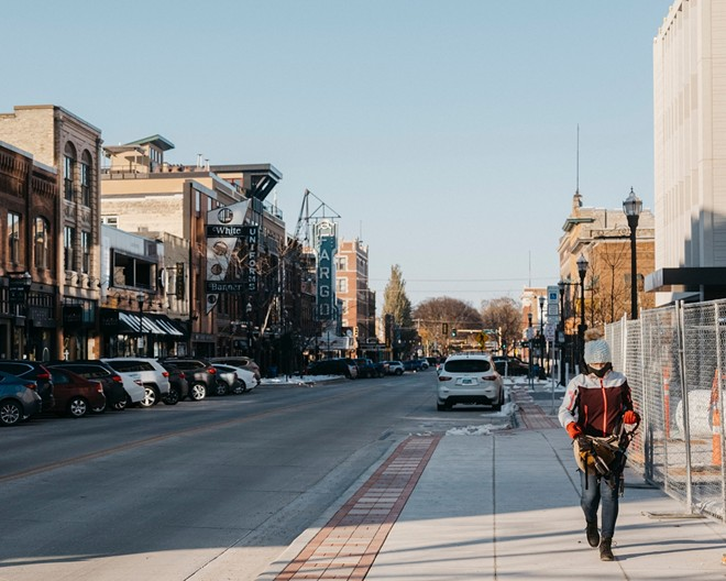 A pedestrian walks through downtown Fargo, N.D. on Oct. 26, 2020. New outbreaks used to be traced back to crowded factories and rowdy bars but now, the virus is so widespread not even health officials are able to keep up. - JOEL ANGEL JUAREZ/THE NEW YORK TIMES