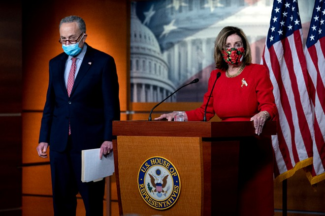 Senate Minority Leader Chuck Schumer (D-N.Y.) listens as House Speaker Nancy Pelosi (D-Calif.) speaks during a press conference at the Capitol in Washington, on Sunday, Dec. 20, 2020. - STEFANI REYNOLDS/THE NEW YORK TIMES