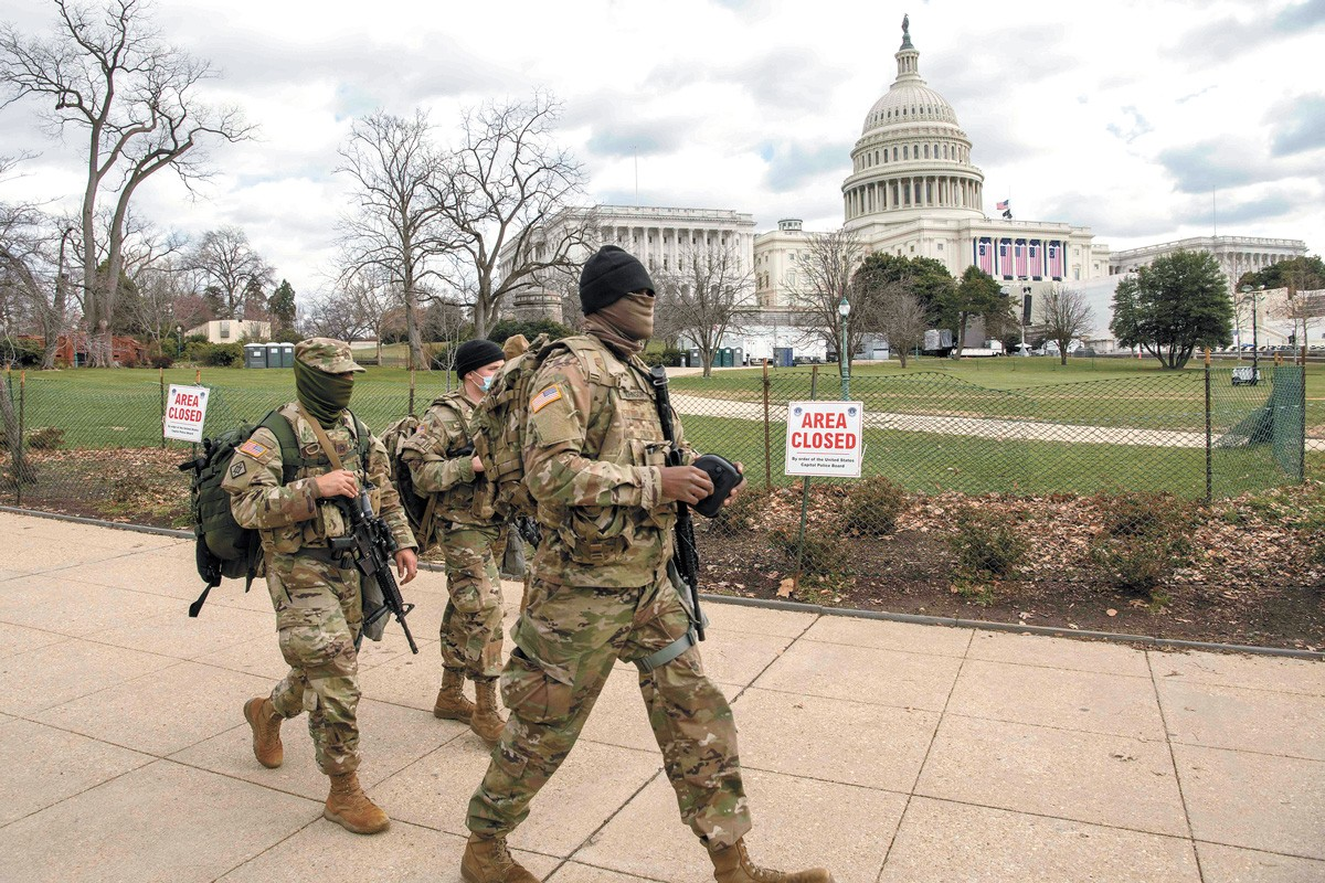 Soldiers assigned to the Virginia Army National Guard walk the fence line near the U.S. Capitol building earlier this week. - U.S. AIR NATIONAL GUARD PHOTO