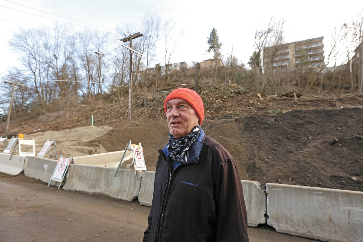 Longtime Peaceful Valley resident Charlie Greenwood next to a collapsed hill in the neighborhood. - YOUNG KWAK PHOTO