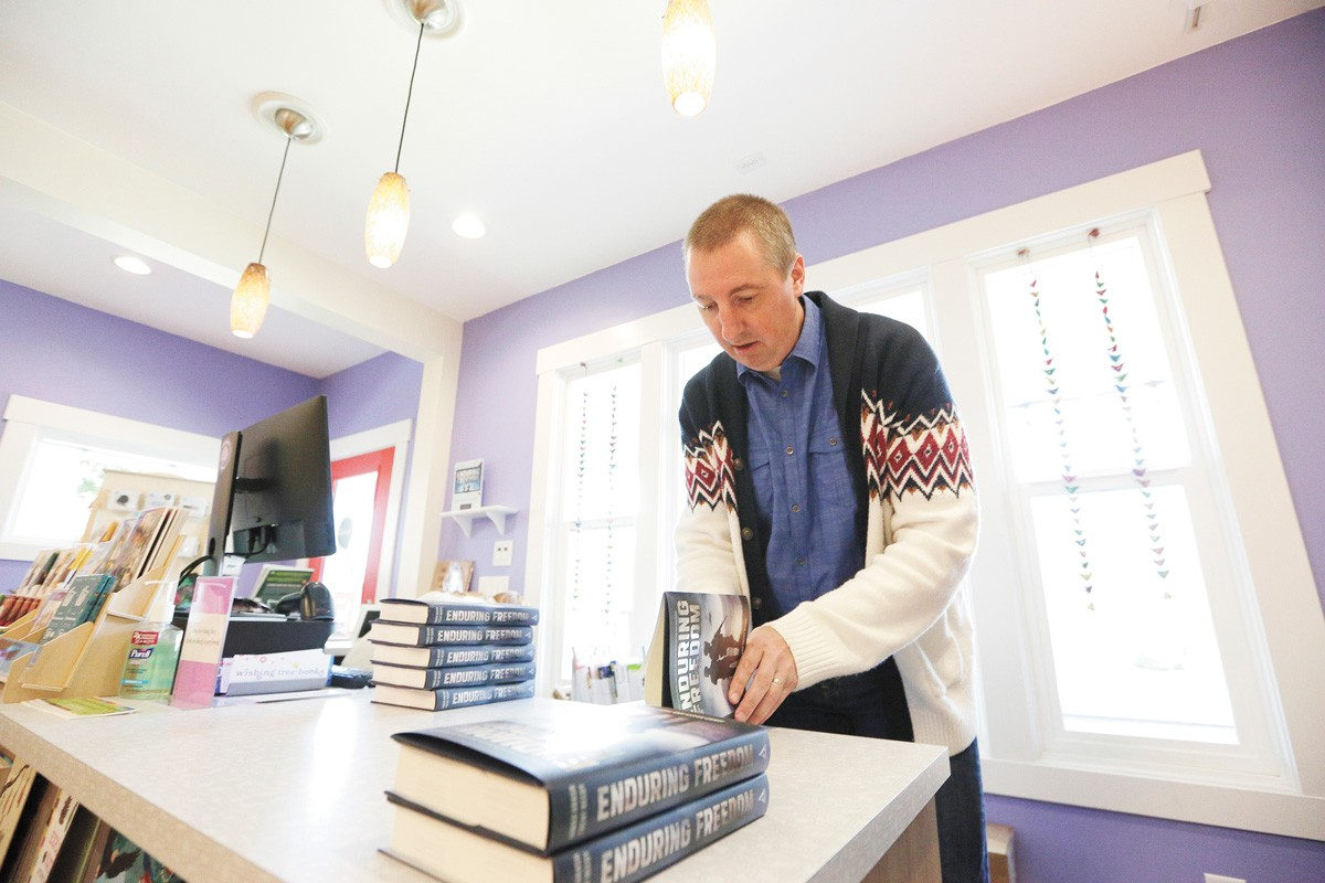 Trent Reedy, co-author of Enduring Freedom, signs copies at Wishing Tree Books. - YOUNG KWAK PHOTO