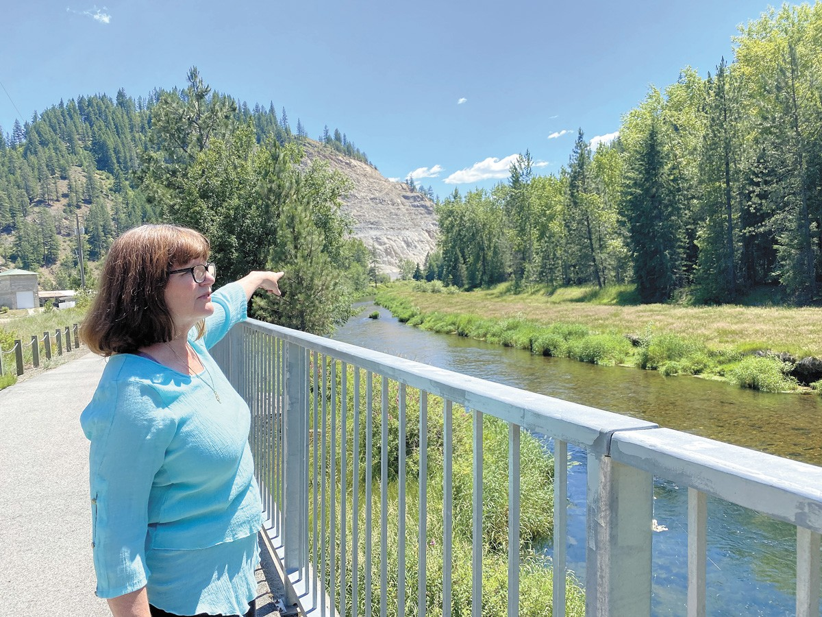 Dawn Wiksten, who founded Friends of the River Coalition, points out an old county dump site across the Coeur d'Alene River. A campsite (now for private family use) was built right next to the contaminated area. - SAMANTHA WOHLFEIL PHOTO