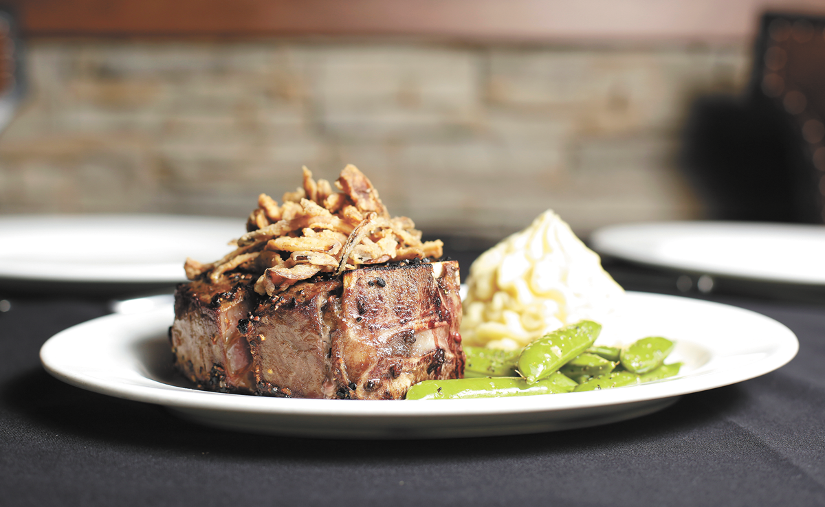 A bone-in tenderloin steak with garlic potatoes and snap peas at Churchill's Steakhouse. - YOUNG KWAK PHOTO