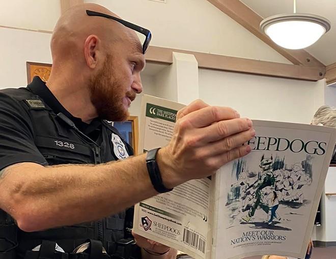 Spokane Police Officer Graig Butler reading children a book co-authored by Dave Grossman. - SPOKANE POLICE DEPARTMENT (FACEBOOK)