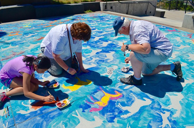 Community members paint their own horses as part of the mural.