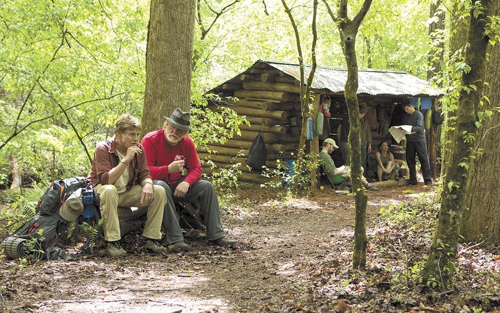 Robert Redford and Nick Nolte cop a squat in the woods.