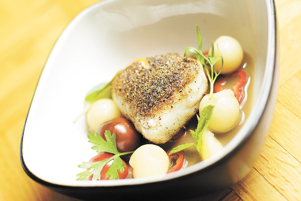 A spice-encrusted piece of halibut in a mushroom sauce, with potatoes and fresh herbs. - YOUNG KWAK
