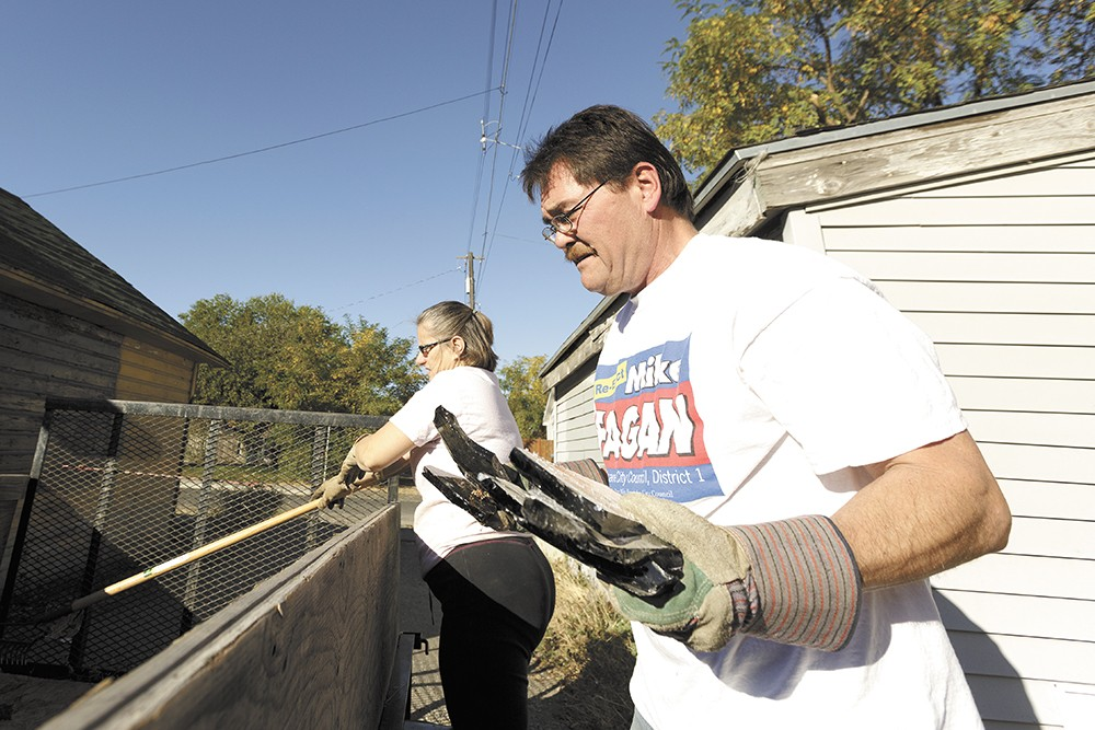 Spokane City Councilman Mike Fagan (right) along with his wife, Donna,  load trash  during a neighborhood cleanup event. - YOUNG KWAK