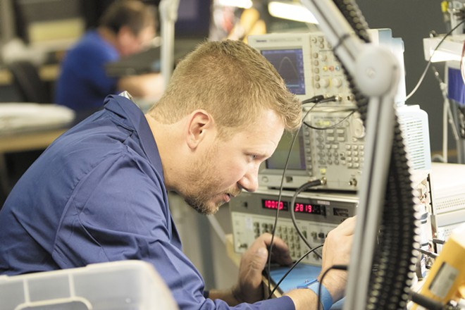 A repair technician uses a probe to test a PA amplifier from an MD-80 at Absolute Aviation Services. - YOUNG KWAK