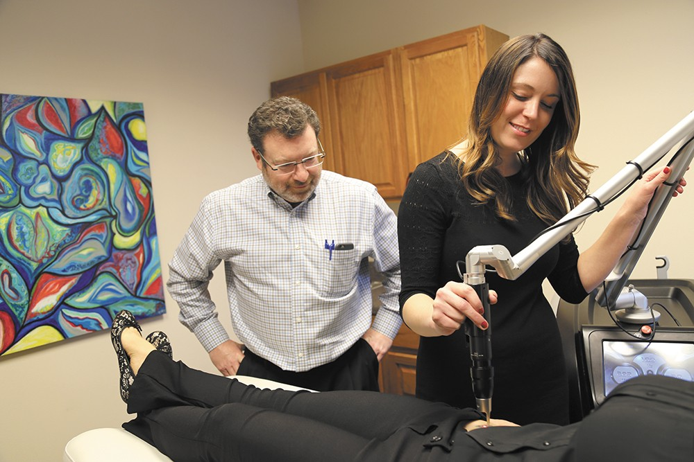 Dr. Kevin Johnson and aesthetic nurse Brittany Rayson use a laser for tattoo removal at Spokane's Advanced Aesthetics. - SARAH PHILIP