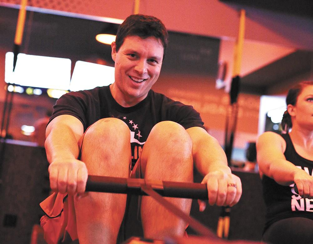 Jason Vestal manages a smile while rowing at Spokane's Orangetheory Fitness. - YOUNG KWAK