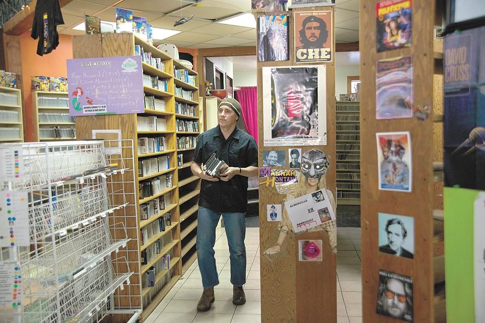 Manager Ben Hardcastle restocks the shelves at Howard Hughes Video. - TARYN PHANEUF