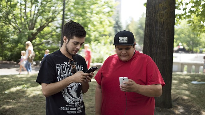 Tyler Zoesch and Daniel Moreno set an in-game lure to attract Pokémon Go characters to an area of Riverfront Park. - ANDRA MOYE