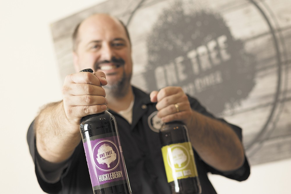 Co-owner Neal Hennessy shows off bottles of One Tree's hard cider. - YOUNG KWAK