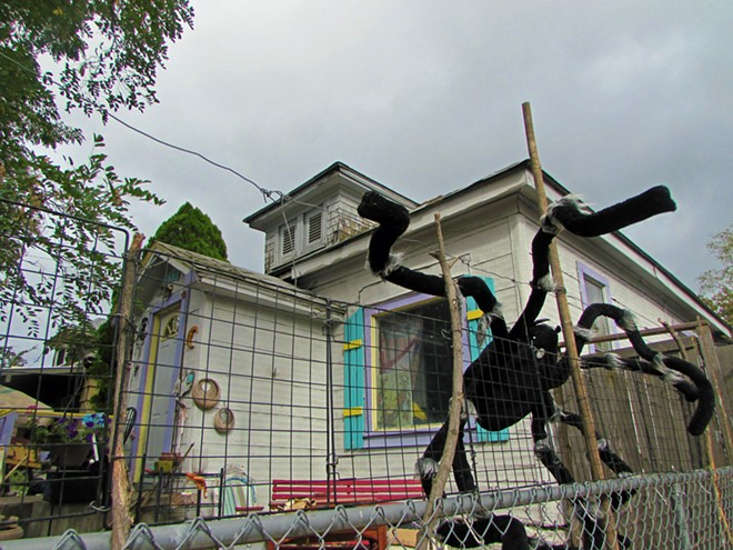A sculpture of a spider climbs up the fence in front a Bridge Avenue lawn stuffed with quirky artwork. - DANIEL WALTERS PHOTO