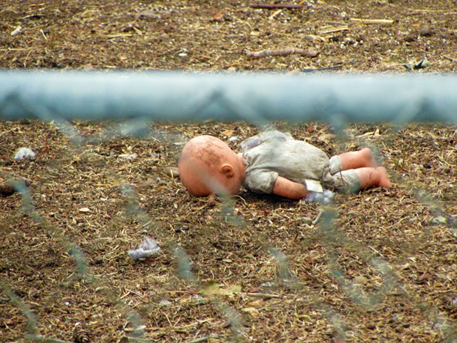 A doll lays facedown in the dirt, scattered among other toys on a lawn on Bridge. - DANIEL WALTERS PHOTO