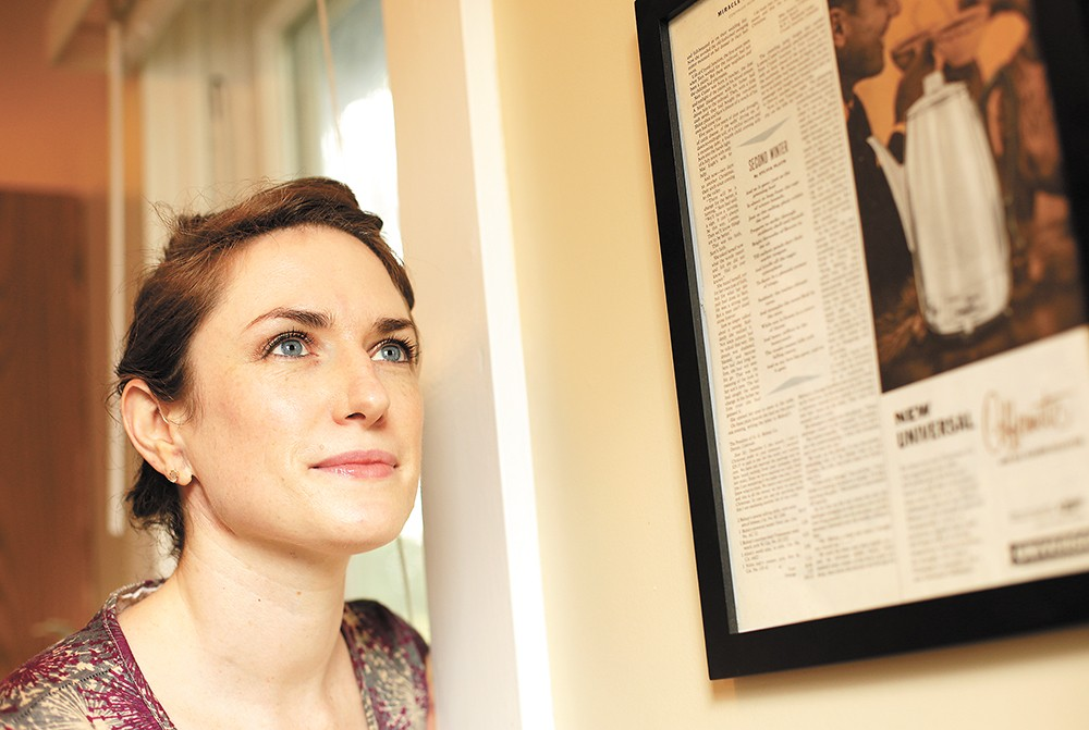 Kate Lebo next to a framed poem by Sylvia Plath from Ladies' Home Journal.