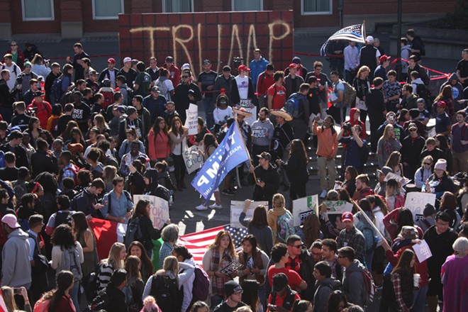 Fernando Reyes standing in the middle of a crowd of protesters holding a Trump flag and a phone - WILSON CRISCIONE