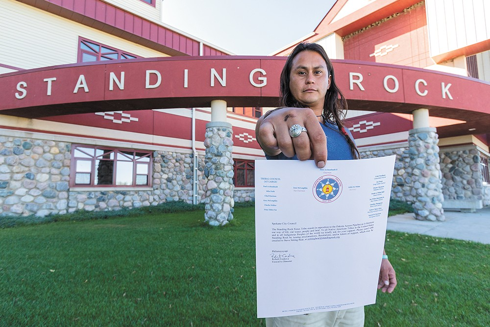Johns in front of the Standing Rock Sioux Tribe building in North Dakota with a letter from the tribe asking the Spokane City Council to pass a resolution against the DAPL. - JEFF FERGUSON