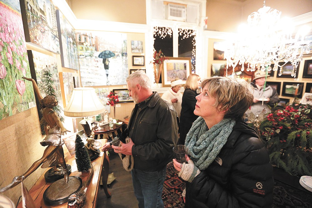 """Dorey Rowland looks at Arlon Rosenoff's """"April Tulips"""" as her husband, Bruce Rowland, checks out sculptures at Angel Gallery of Fine Art & Antiques during the monthly Coeur d'Alene Art Walk. - YOUNG KWAK"""