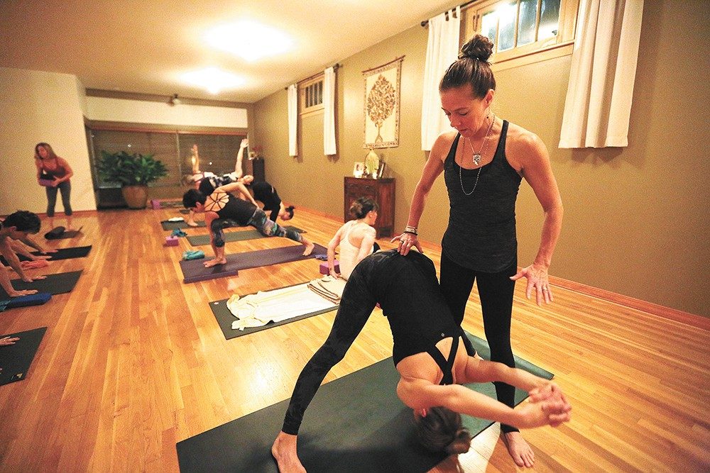Shelley Enlow, right, helps Leanna Howlette with a forward bend during an Ashtanga class last month. - YOUNG KWAK