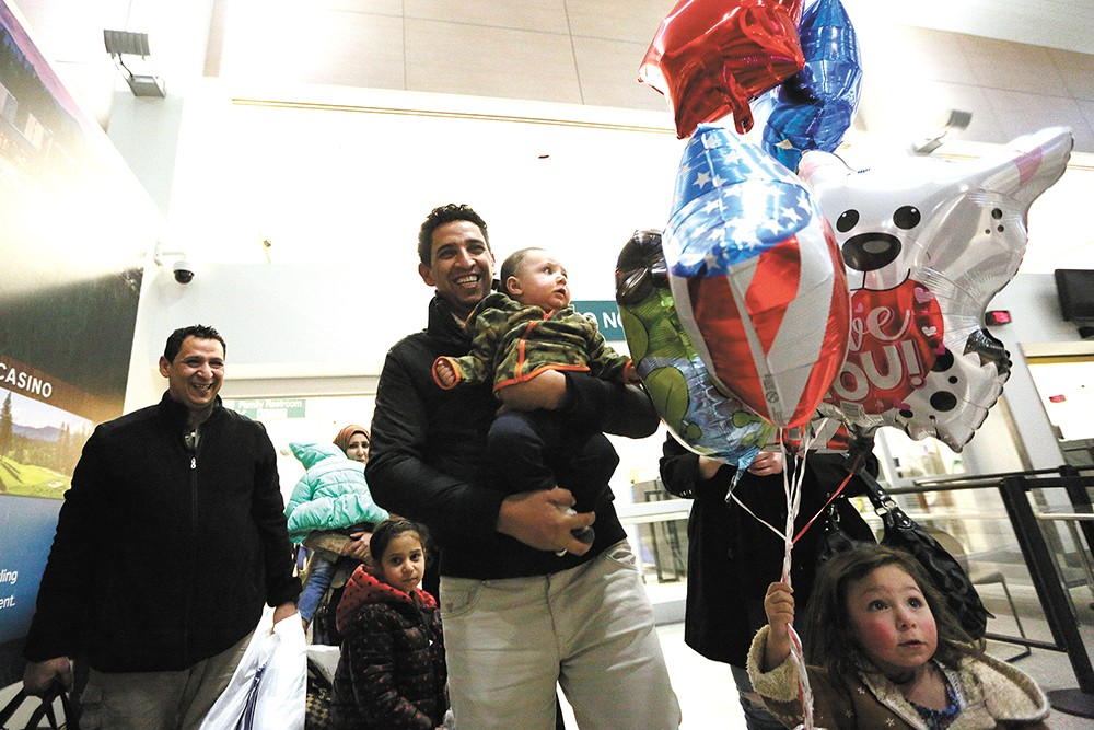 Hamid Nahi (left) smiles as his brother, Assad Al-Sawaedi, holds Nahi's son at Spokane International Airport. - YOUNG KWAK