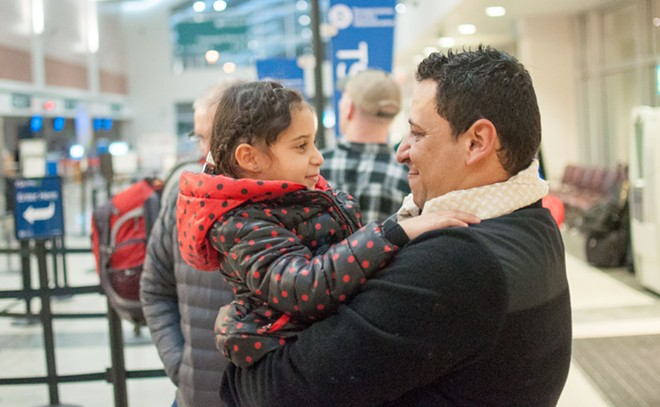 Hamid Nahi holds his 5-year-old neice Rahaf Al-Sawaedi, moments after she arrives in Spokane - DANIEL WALTERS PHOTO
