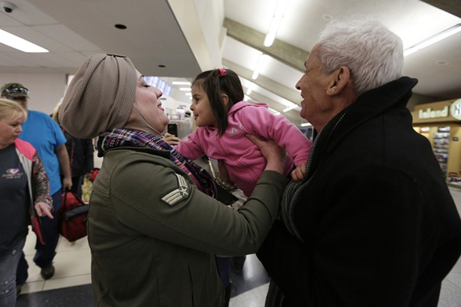 Talib Baghdadi, right, a refugee from Iraq who arrived on a flight, hands 3-year-old Haya Baghdadi to his daughter-in-law Hamsa Fahan. - YOUNG KWAK PHOTO