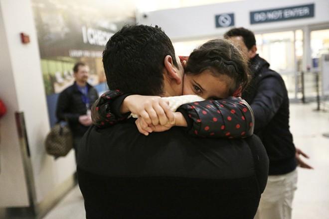 Iraqi refugee Rahaf Al-Sawaedi hugs her uncle, Hamid Nahir. - YOUNG KWAK PHOTO